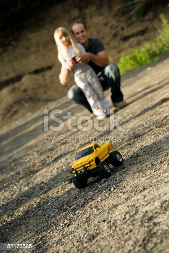 496487362istockphoto Child Girl and Father Playing with Remote Car Summer Lifestyle 182173565