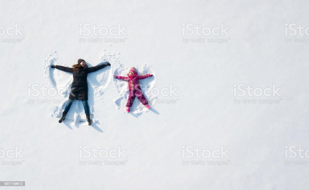 Enfant fille et mère jouer et de faire un ange de neige dans la neige. Vue de dessus plat généraux photo libre de droits