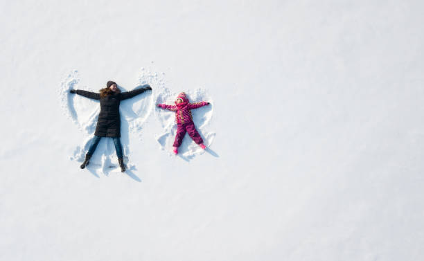 Child girl and mother playing and making a snow angel in the snow. Top flat overhead view Child girl and mother playing and making a snow angel in the snow. Top flat overhead view day stock pictures, royalty-free photos & images