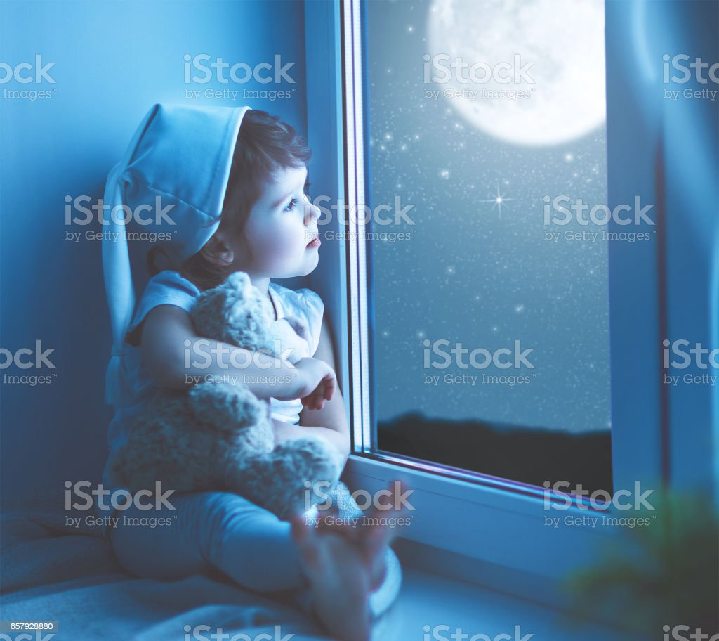 child girl at window dreaming starry sky at bedtime stock photo