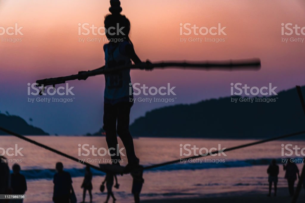child girl balance on the wire on the goa beach at sunset india stock photo