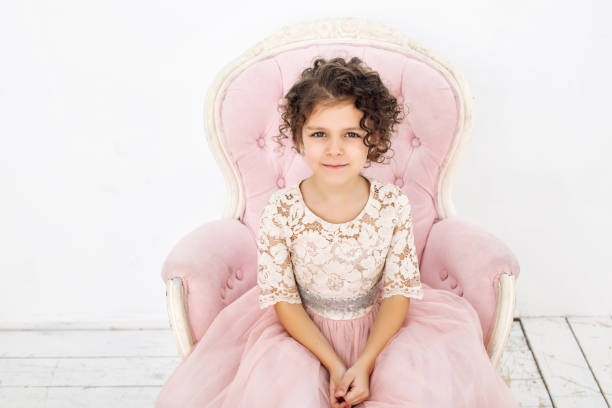 kindermädchen schön, niedlich fröhlich und glücklich auf einem rosa stuhl in einem modischen luxuskleid - prinzessin kleid kind stock-fotos und bilder