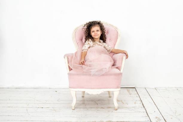 kindermädchen schön, niedlich fröhlich und glücklich auf einem rosa stuhl in einem modischen luxuskleid - prinzessinnen tutu stock-fotos und bilder