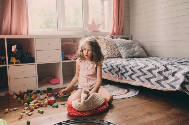 child girl cleaning her messy room and put toys in basket stock photo
