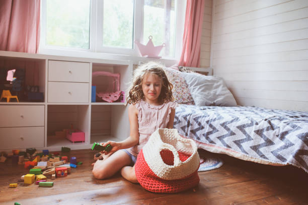child girl cleaning her room and organize wooden toys into knitted storage bag. Housework and help concept child girl cleaning her room and organize wooden toys into knitted storage bag. Housework and help concept kids cleaning up toys stock pictures, royalty-free photos & images