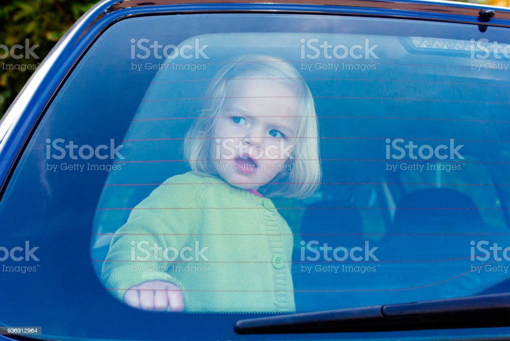 Child girl closed in the back of a car on a hot day. Child girl closed in the back of a car on a hot day. Concept image of danger of overheating in car for young children in the summer Assistance Stock Photo