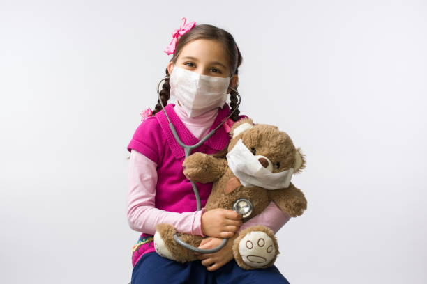 Child Girl Doctor Hugging and Treating Her Toy Bear with Mask, Coronavirus and Stay at Home Concept stock photo