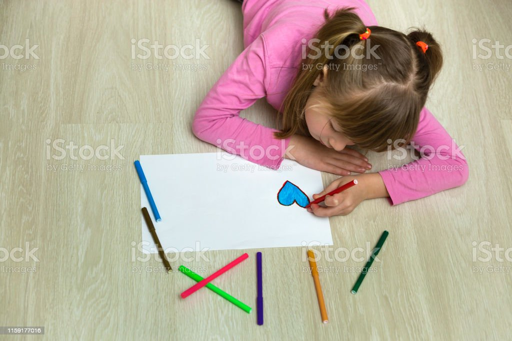 Child girl drawing with colorful pencils crayons heart on white...