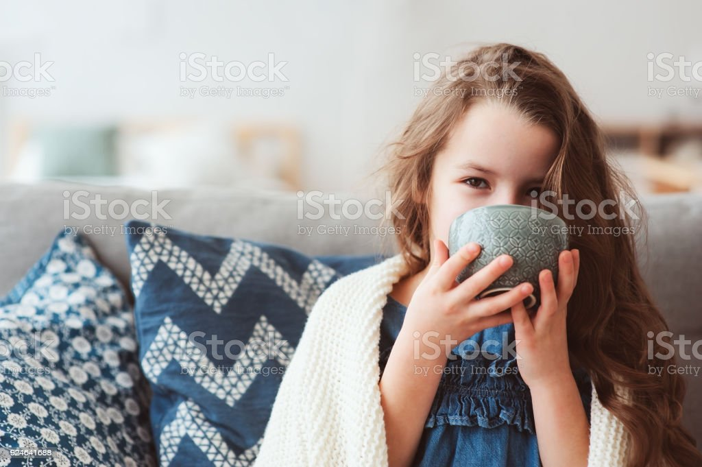 child girl drinking hot tea to recover from flu. Healing kids and protect immunity from seasonal virus, health concept stock photo