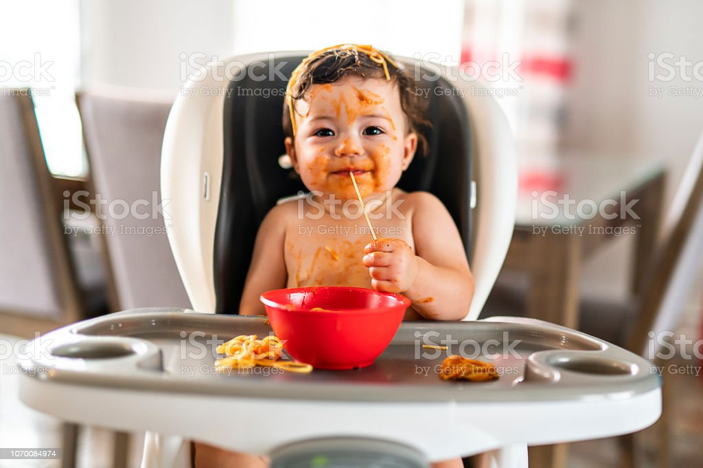 child girl, eating spaghetti for lunch and making a mess at home in kitchen royalty-free stock photo