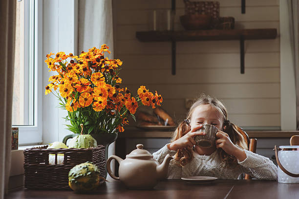 child girl having breakfast at home in autumn morning - house with flowers stock photos and pictures