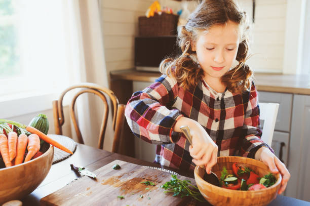 child girl helps mom to cook and cut fresh vegetables for salad with knife. Kids learning house work on farm on summer vacations stock photo