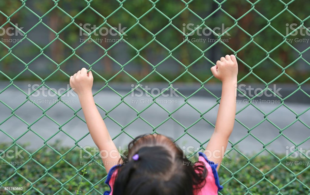Child girl hold the iron mesh. Hand holding steel grating. stock photo
