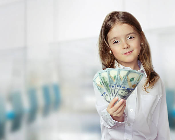 child girl holding money in hands financial background. - little girls giving head stock photos and pictures