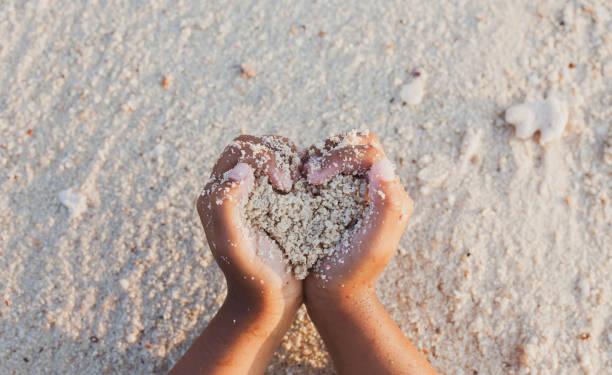 Kindermädchen, die Sand halten, machen Herzform in den Händen und spielen am Strand – Foto