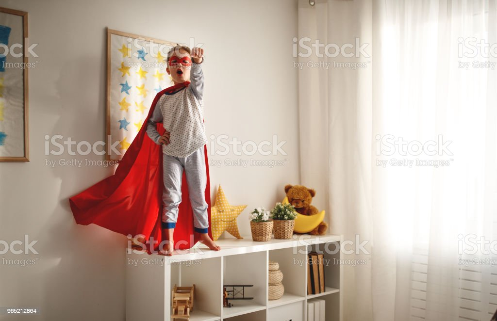 child girl in a super hero costume with mask and red cloak zbiór zdjęć royalty-free