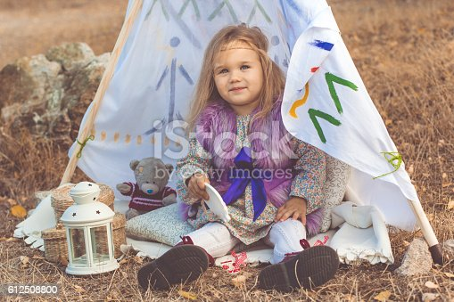 istock Child girl in decorative hovel on the nature 612508800
