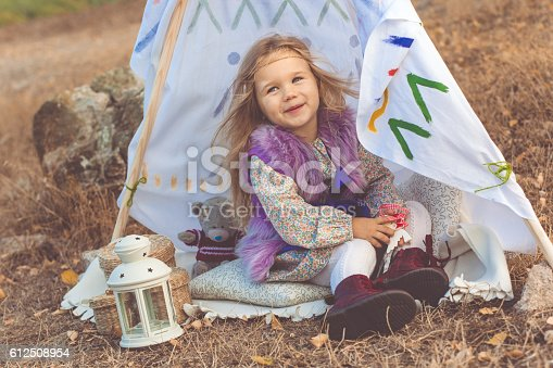 istock Child girl in decorative hovel on the nature 612508954