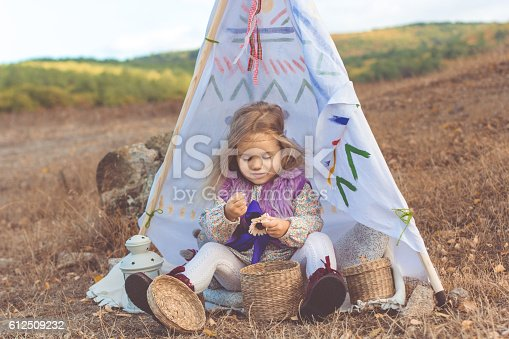 istock Child girl in decorative hovel on the nature 612509232