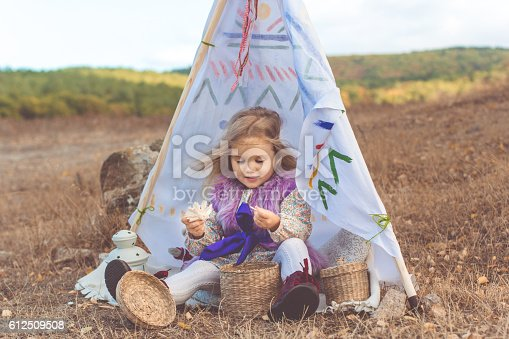 istock Child girl in decorative hovel on the nature 612509508