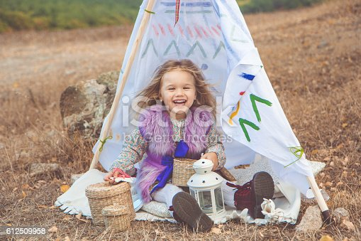 istock Child girl in decorative hovel on the nature 612509958