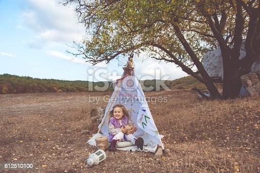 istock Child girl in decorative hovel on the nature 612510100