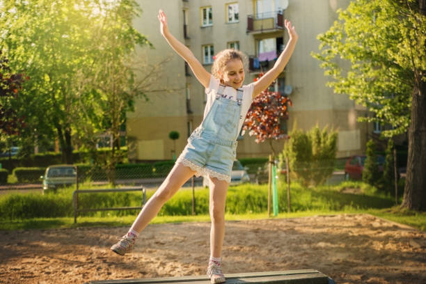 kind mädchen im overall springen auf einer bank in einem wohngebiet. - jeans overall stock-fotos und bilder
