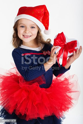 1061876006istockphoto Child girl is holding gift box with red ribbon 496661978