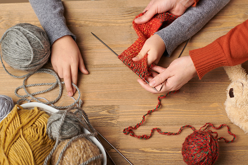 Child girl is learning to knit. Colorful wool yarns are on the wooden table. Hand closeup.