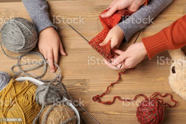 Child girl is learning to knit colorful wool yarns are on the wooden picture id1130899136?b=1&k=6&m=1130899136&s=612x612&h=q71dlocmotqxthgr0tgthlu ckbxjndkkf8g0euf o8=