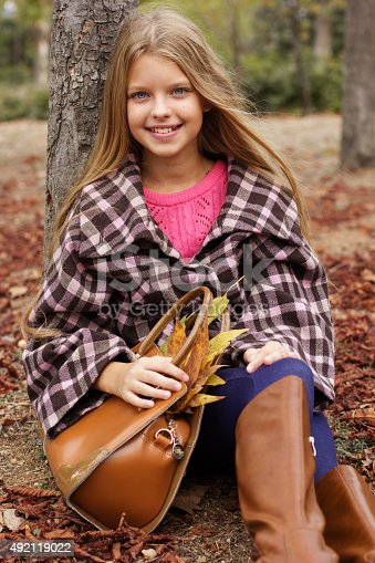 istock Child girl is sitting in autumn park 492119022