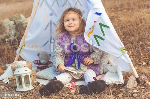 istock Child girl is sitting in decorative hovel 612508684