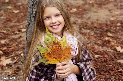 istock Child girl is sitting in park with fallen leaves 492119078
