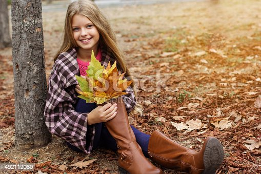 istock Child girl is sitting in park with yellow foliage 492119060