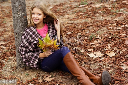 istock Child girl is sitting in park with yellow leaves 492119034