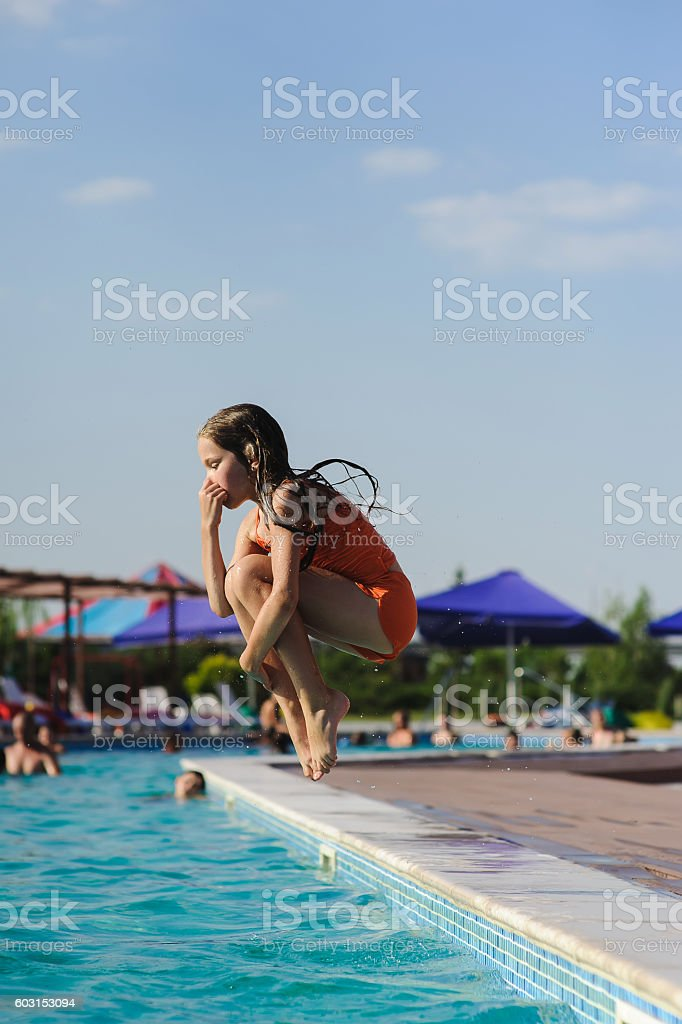 Child girl jumping into swimming pool stock photo