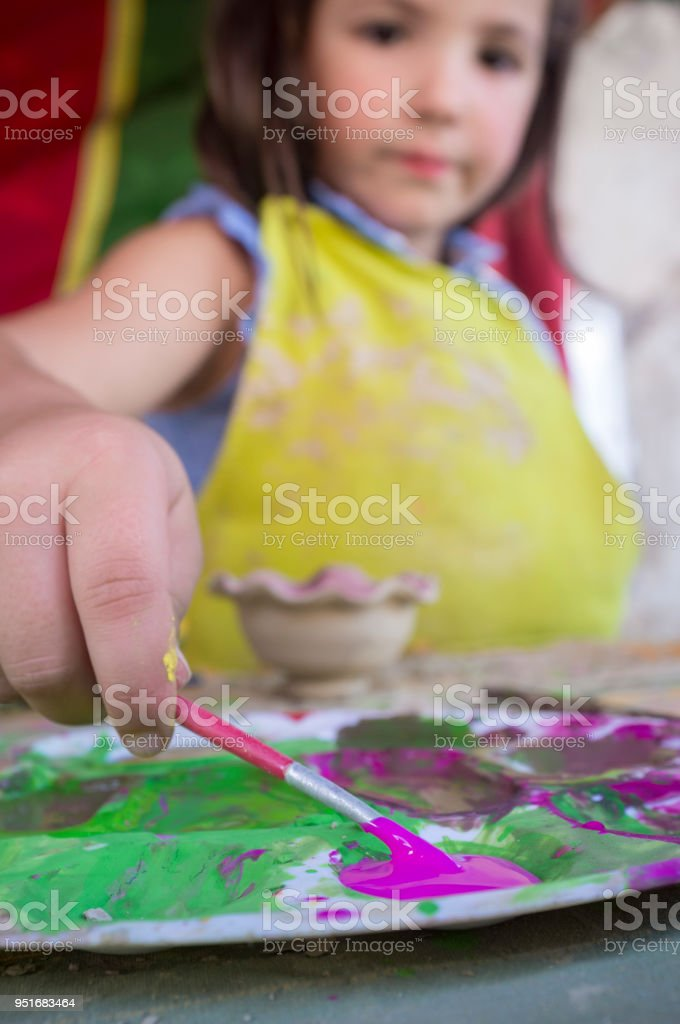 Child girl loading with purple color her brush stock photo