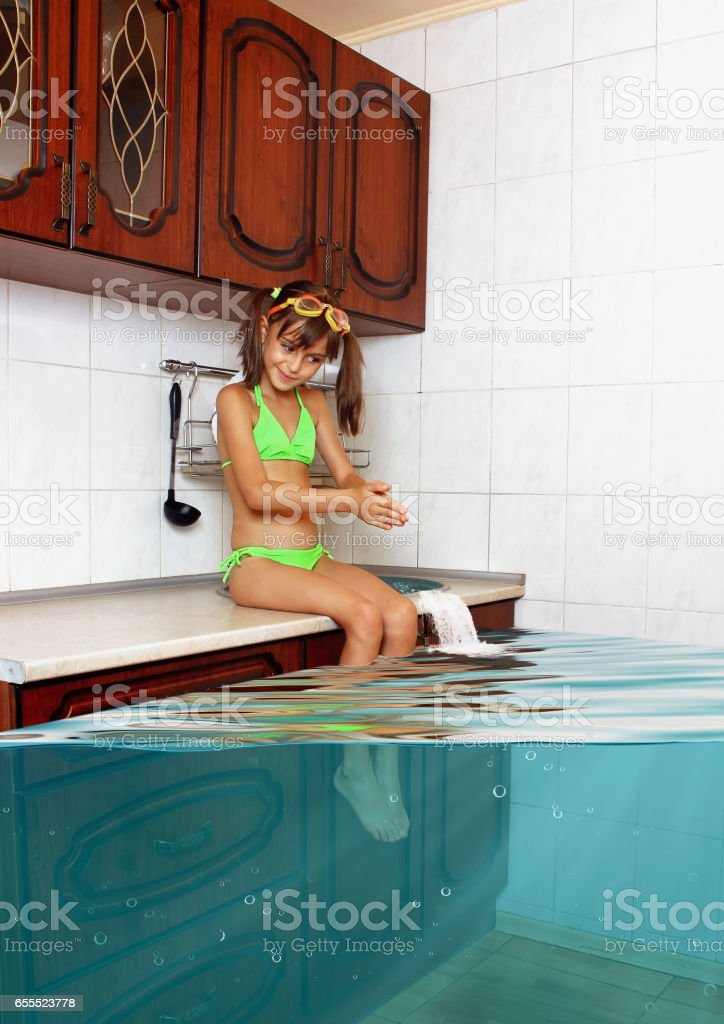 Child girl make mess, flooded kitchen imitating swimming pool, funny concept stock photo