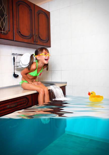 kind mädchen machen durcheinander, überfluteten küche imitieren schwimmbad, lustige konzept - traum pools stock-fotos und bilder
