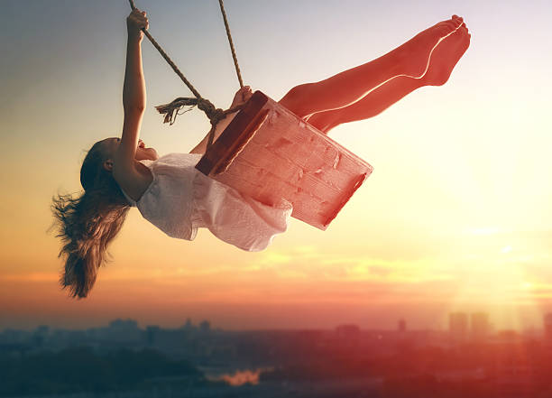 child girl on swing - innocence stock pictures, royalty-free photos & images