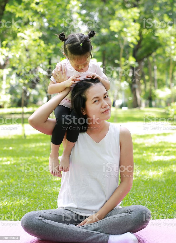 Child girl play riding on mother neck in park. royalty-free stock photo