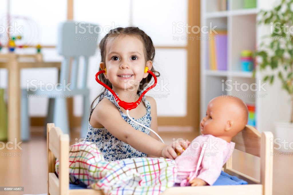 child girl playing doctor role game examining her doll using stock photo