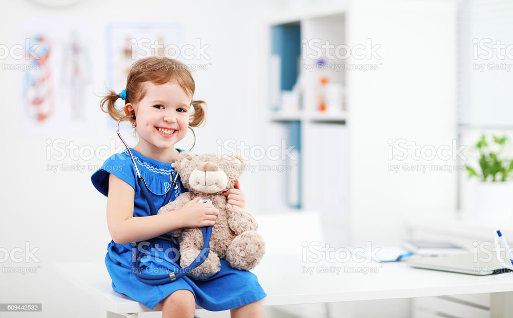 Child girl playing doctor with teddy bear - Photo