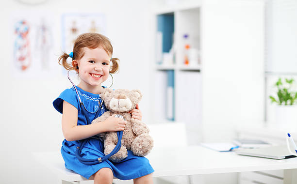 Child girl playing doctor with teddy bear stock photo