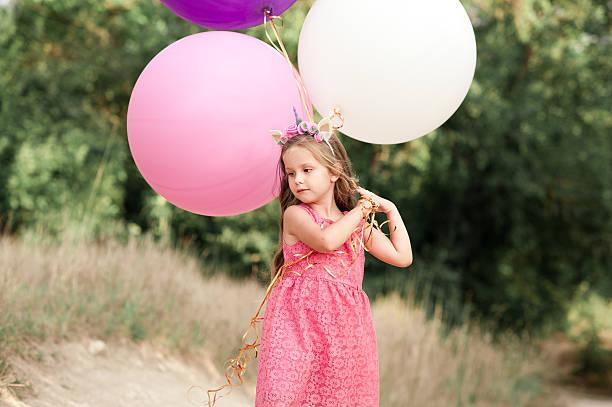 child girl playing with balloons - festliche babymode junge stock-fotos und bilder