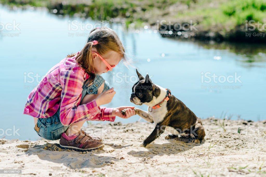 Chica de niño jugando con perro boston terrier en el Banco de arena de río al aire libre - foto de stock