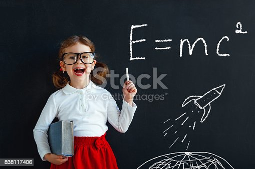istock Child girl prodigy student with book near blackboard 838117406