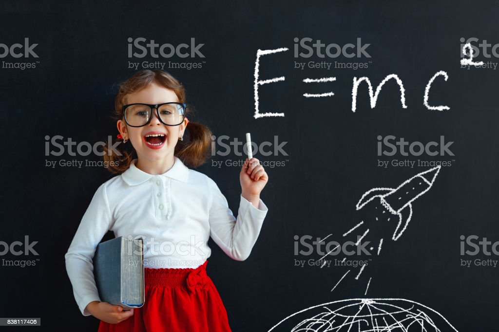 Child girl prodigy student with book near blackboard stock photo