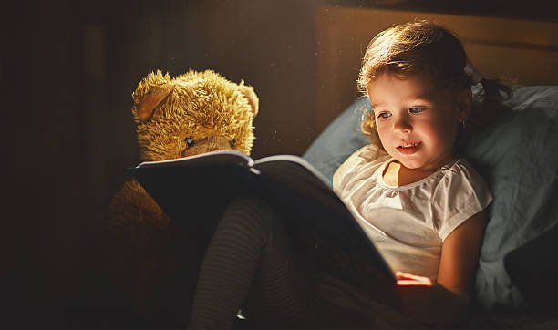 child girl reading a book in bed - foto de stock