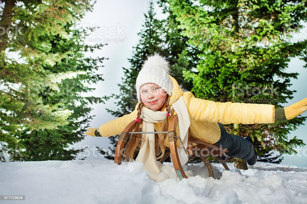 Child girl riding a sledge outdoors in snow stock photo
